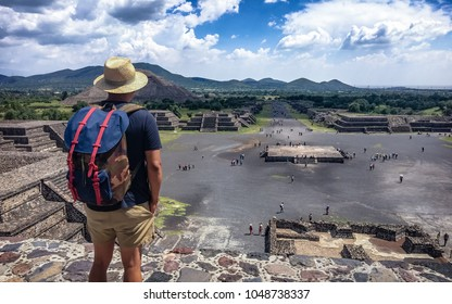 Teotihuacan, Mexico.  A man tourist with a backpack and hat enjoys the view from the top of the Moon Pyramid. The Sun Pyramid and Avenue of the Dead can be seen in the distance.