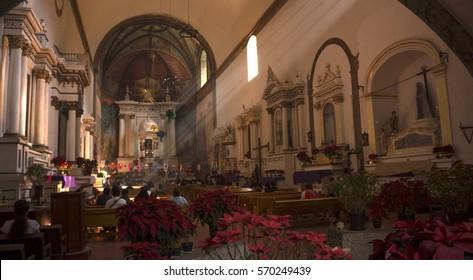 "Tepoztlan, Mexico - December 25, 2016: Parishioners praying in the ""Nuestra Señora de la Natividad"" (Our Lady of the Nativity) parish on Christmas Day"