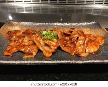 Teppanyaki slice pork stir fries with barbecue sauce Japanese steak on hot plate background .