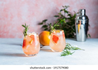 Tequila cocktail or cold lemonade with grapefruit juice, tinted with the aroma of a fresh sprig of rosemary on fashion pastel pink background.
