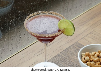 Tequila cocktail and nuts in a moment of rain