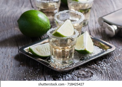 Tequila gold, Mexican, alcohol in shot glasses, lime and salt, toned image, selective focus, rustic