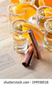 tequila with orange and cinnamon on a wooden table