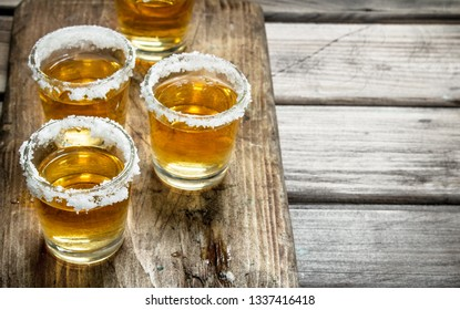 Tequila in a shot glass on a cutting Board with slices of lime. On wooden background