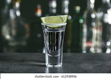 Tequila shot with juicy lime slice and salt on blurred background of glass bottles