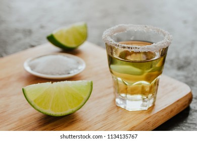 Tequila shot, mexican drinks and pieces of lime with salt in mexico
