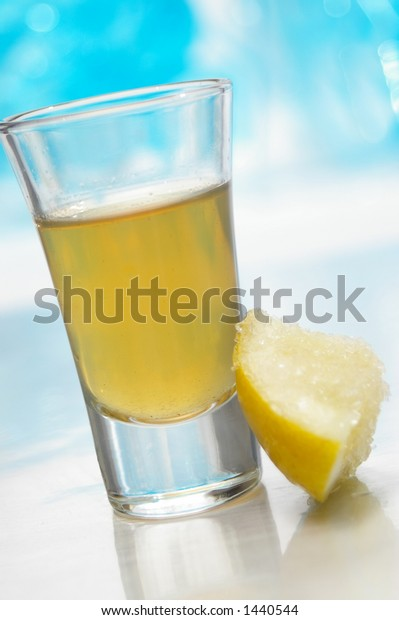 Tequila shot with salt covered lemon wedge.