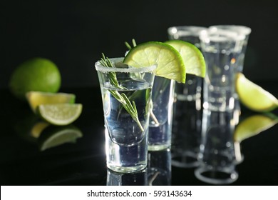 Tequila shots with juicy lime slices and salt on black background