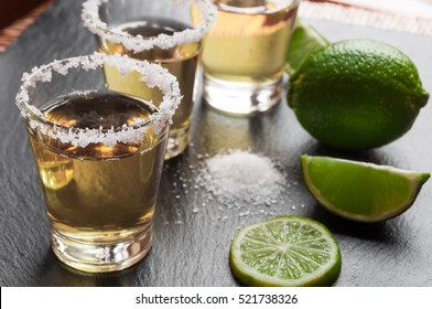 Tequila shots with lime and salt on black