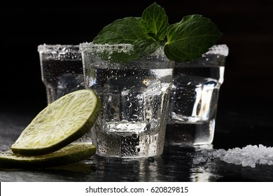 Tequila shots with salt and lime on stone