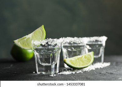 Tequila shots with salt and lime slices on black background