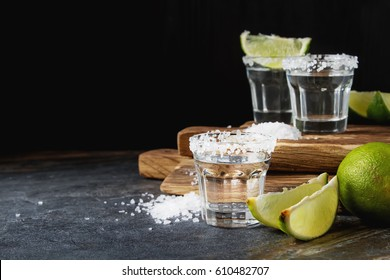 Tequila silver with lime and sea salt. Dark background. Selective focus.
