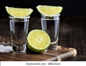 Tequila silver shots with lime slices and salt on grunge wooden board
