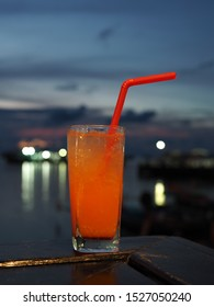 Tequila sunrise cocktail on wooden table at seaside restaurant.