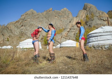 TERELJ,  GORKHI-TERELJ NATIONAL PARK , MONGOLIA -  28 OCTOBER 2014 : three mongolian wrestlers in their colorful gear preaparing before the fight