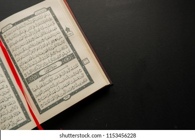 Terengganu, Malaysia - 9th August 2018: an open page of Quran shows Surah al kahf on black background. Quran is an Islamic holy book for muslim. selective focus.