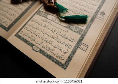 Terengganu, Malaysia - 9th August 2018: an open page of Quran shows Surah al kahf with rosary on black background. Quran is an Islamic holy book for muslim. selective focus.