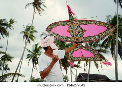 Terengganu, Malaysia - April 23, 2016: A man in traditional attire headdress and 'sarong' holding handmade Wau Bulan or Moon Kite.