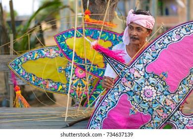 "TERENGGANU, MALAYSIA : APRIL 24, 2016 : A traditional kite or ""Wau"" maker with his collections at Terengganu state of Malaysia"