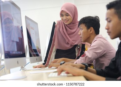 Terengganu, Malaysia - April 25, 2016: Side view of young students using computer in lab and having training course in classroom with teacher, trainer or instructor. Students in training class workin