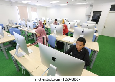 Terengganu, Malaysia - April 25, 2016: Multiethnic group of young university students sitting at table using computers for research in the computer lab. Young people taking information from computer f