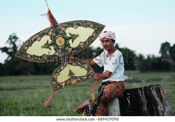 TERENGGANU, MALAYSIA -Circa 2016 : Portrait of Malay traditional kite maker (Wau) wearing batik sarung (Malay tradisional skirt) at the field.