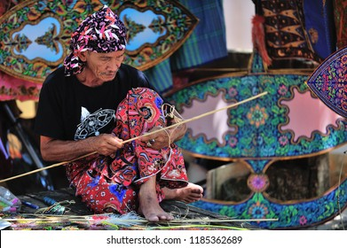 "TERENGGANU, MALAYSIA : May 01, 2016 : A traditional kite or ""Wau"" maker wearing batik sarung (Malay tradisional skirt)  working on a kite in his workshop"