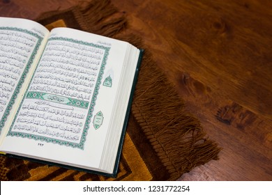 TERENGGANU, MALAYSIA - Nov 16, 2018 : An open page of Quran shows Surah Al Kahf on the prayer mat over wooden background with copy space. Selective focus