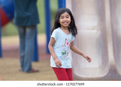 Terengganu, Malaysia - Ogos 7, 2018: Happy children playing outdoors. Cute kids having fun in park. Eye level view portrait of excited laughing happy girls.
