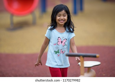 Terengganu, Malaysia - Ogos 7, 2018 :  Happy children playing outdoors. Cute kids having fun in park. Eye level view portrait of excited laughing happy girls.