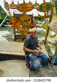 TERENGGANU, MALAYSIA -  SEPTEMBER 2019 : Unidentified kite maker Malay man uses small knife sharpen bamboo stick to make the kite main frame in Terengganu, Malaysia.