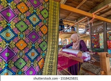TERENGGANU, MALAYSIA -  SEPTEMBER 2019 : Unidentified Malay woman weaves local Malay cloth (songket) beneath a wooden house in Terengganu, Malaysia.