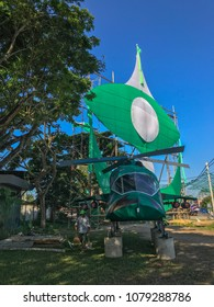 Terengganu, Malaysia-April 29, 2018 : An unidentified cleaner walks by a mock up helicopter built by a local political party members. Malaysia 14th general election will be held on May 9, 2018.