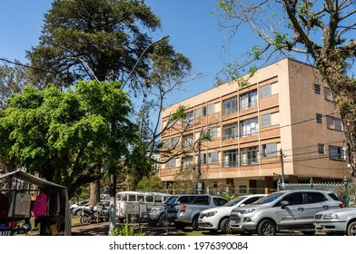 TERESOPOLIS, RIO DE JANEIRO - BRAZIL: AUG 15, 2020: A residential building located at the streets of Higino da Silveira square with many cars parked 45 degrees in front under sunny clear blue sky.