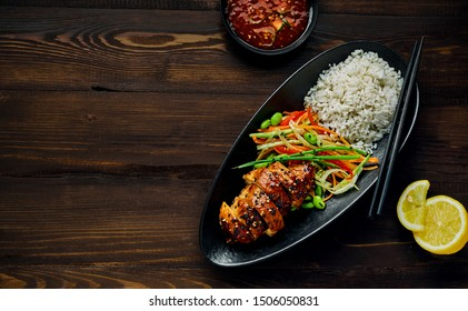 Teriyaki chicken with cucumber, ginger, cabbage and carrot salad, edamame soy beans and basmati rice in a black pottery dish with sweet chili sauce and lemon. Top view, directly above.