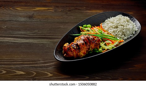 Teriyaki chicken with cucumber, ginger, cabbage and carrot salad, edamame soy beans and basmati rice in a black pottery dish.