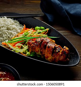 Teriyaki chicken with cucumber, ginger, cabbage and carrot salad, edamame soy beans and basmati rice, lemon and sweet chili sauce ona rustic wooden table.