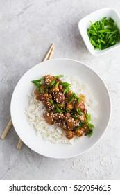 teriyaki chicken with rice, served with sesame seeds and chopped green onions, top view.