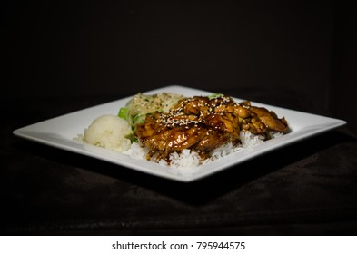 Teriyaki chicken in white plate and dark back ground.