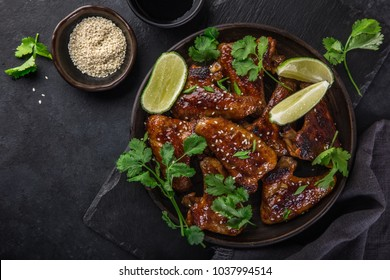 teriyaki chicken wings, served with lime, cilantro and sesame seeds, top view