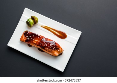 Teriyaki salmon from above. Japanese cuisine inspired dinner consisting of a grilled salmon fillet glazed in delicious teriyaki sauce (soy sauce base). Healthy brussel sprouts as sides.