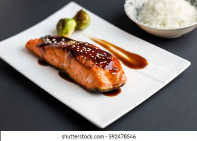 Teriyaki salmon on black background. Japanese cuisine inspired dinner consisting of grilled salmon fillet glazed in delicious teriyaki sauce (soy sauce base). Brussel sprouts and white rice as sides.