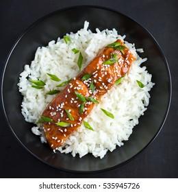 saumons et riz de teriyaki, accompagnés de graines de sésame et d'oignons verts hachés, vue de dessus.