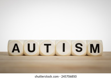 Term Autism spelled out with toy dice on a board