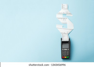 Terminal cash register machine POS for payments and long roll paper cash tape in shape of dollar sign on blue background. Copy space for text