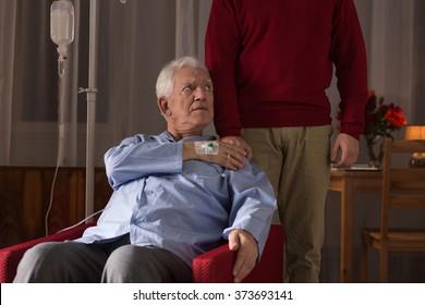 Terminally ill man and his caregiver at home
