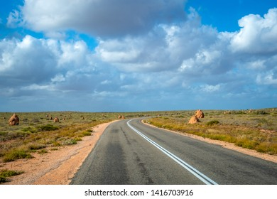 Termite hills along the empty road in Western Australia close to Exmouth before sunset
