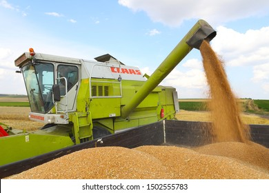 Ternopil region August 2019 Harvester harvests wheat on a sunny summer day. Yellow wheat, bright blue sky with white clouds. Good harvest concept