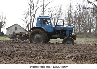 Ternopil region, Ukraine, 6 04 2019 Agricultural tractor plowing the field. Agricultural machinery old tractor, small plow, small farmer in a small area of the field