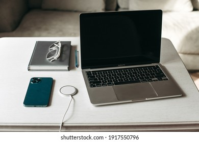 Ternopil, Ukraine - 01.31.2021: Gray MacBook Pro 2020 laptop on M1 chip, Apple iphone 12 Pro Max blue smartphone with wireless charging on a white wooden table in the office with a notebook, glasses